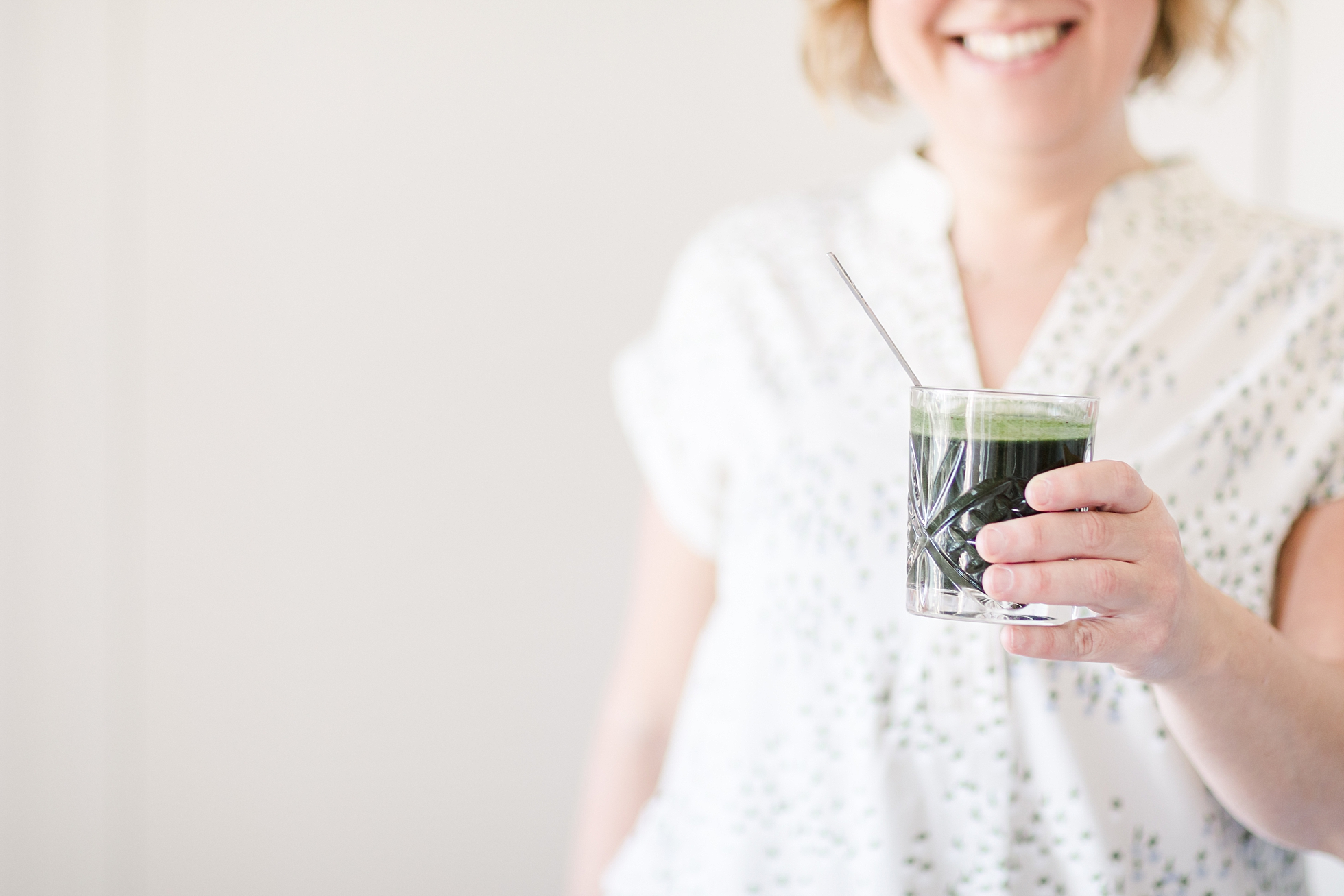 A smiling woman holding a green drink