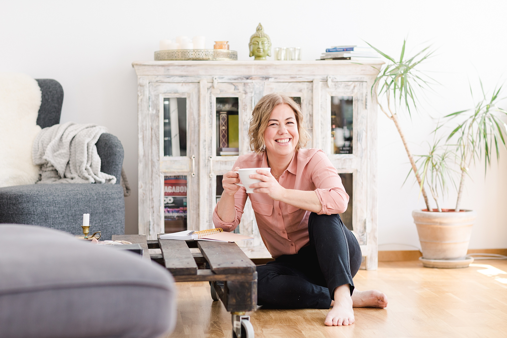 A business woman smiling, holding a cup of coffee